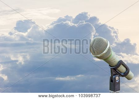 Microphone On A Stand With Blurred Gray Big Cloud Before Raining In The Evening, Copyspace On The Le