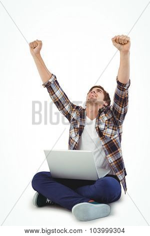 Hipster with laptop on lap cheering with arms raised against white background