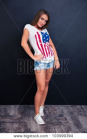 Full length portrait of a pretty girl standing on gray background