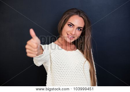 Portrait of a happy woman showing thumb up over gray background and looking at camera