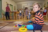 stock photo of nursery school child  - child play in kindergarten and many children behind - JPG