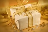 pic of gift wrapped  - christmas gift wrapped with white and gold paper and bow - JPG