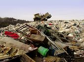 stock photo of landfill  - bulldozer at landfill shoveling garbage that is piled up - JPG