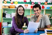 stock photo of teacher  - Teachers or teacher and parent having a discussion in classroom - JPG