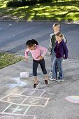 stock photo of hopscotch  - Asian girl jumping on hopscotch board with friends watching - JPG