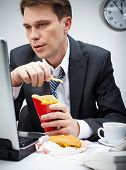 picture of junk food  - Portrait of serious businessman looking at laptop screen while eating fries potato - JPG