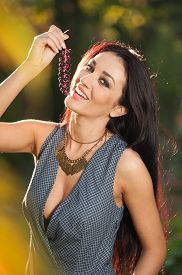 stock photo of grape  - Beautiful woman in gray posing in autumnal park holding a ripe grapes bunch - JPG