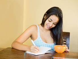 picture of pyjama  - young woman with a coffee writing in a notebook dressed in her pyjama - JPG