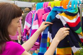 picture of stall  - Woman looking at clothing hanging on hangers shopping clothes on stall at the bazaar - JPG