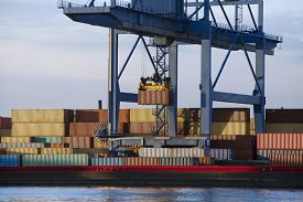 stock photo of barge  - Gantry crane lifting a container from stack to a barge - JPG