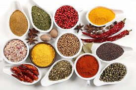 stock photo of flavor  - Flavorful colorful spices in ceramic and metal bowls on white background - JPG