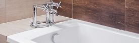 image of tapping  - Panoramic view of white bathtub with silver old style tap - JPG
