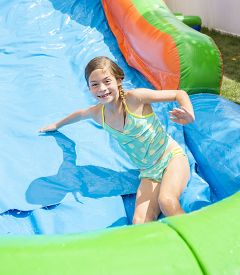 picture of inflatable slide  - Smiling little girl playing on an inflatable slide bounce house - JPG