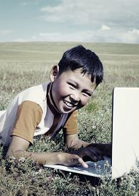 stock photo of mongolian  - Mongolian Boy Laptop Grass Technology Connection Concept - JPG