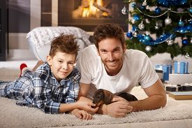 picture of puppy christmas  - Happy young father and son lying on floor at christmas time - JPG
