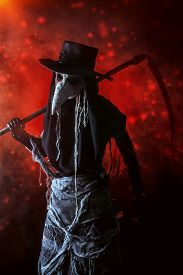foto of scythe  - Portrait of a terrible plague doctor with a scythe - JPG