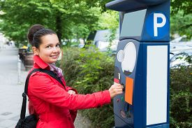 picture of insert  - Young Beautiful Woman Inserting Coin In Parking Meter - JPG