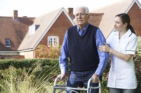 stock photo of zimmer frame  - Carer Helping Senior Man To Walk In Garden Using Walking Frame - JPG