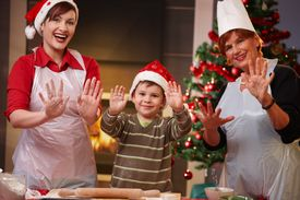 picture of doughy  - Portrait of happy child with mom and grandmother at christmas baking raising doughy hands smiling - JPG