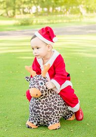 stock photo of baby doll  - Asian baby boy in santa claus suit is playing with reindeer doll at outdoor park - JPG