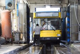stock photo of tram  - The driver of the trolley car is washing the vehicle in the tram depot - JPG