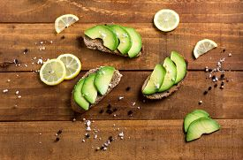picture of fresh slice bread  - Avocado sandwich on dark wholemeal bread made with fresh sliced avocados on the woodwn table - JPG