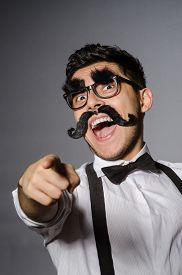 stock photo of moustache  - Young caucasian man with false moustache against gray - JPG