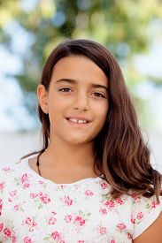 picture of ten years old  - Nice child girl ten year old smiling at camera on the street - JPG