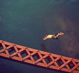 picture of trestle bridge  - a boy diving  off an old train trestle bridge into a river toned with a retro vintage instagram filter effect - JPG