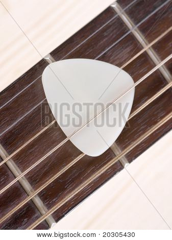 Color photo of acoustic guitar and pick on wood