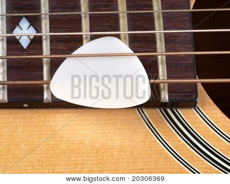 Color photo of acoustic guitar and pick