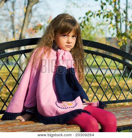Thoughtful little girl sitting on a bench.