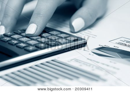 Female hand working with financial reports.