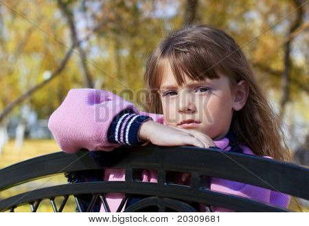 Little girl leaning on a bench.