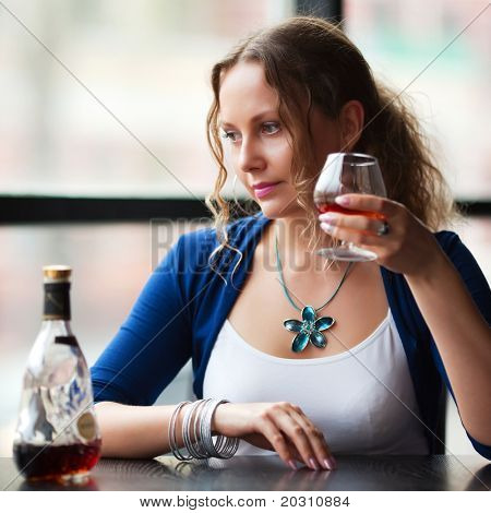 Beautiful woman drinking cognac at a restaurant.