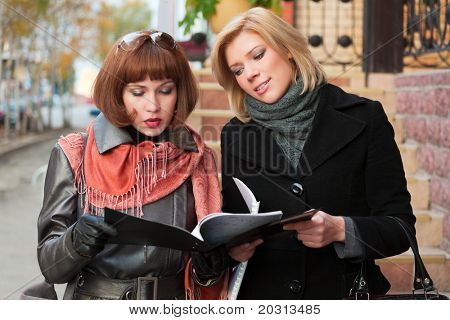 Two young businesswomen with financial reports.