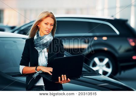 Young businesswoman with laptop on the car parking.