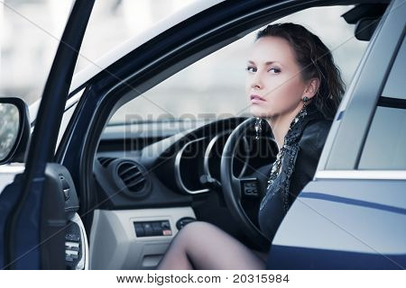 Young woman sitting in a sports car