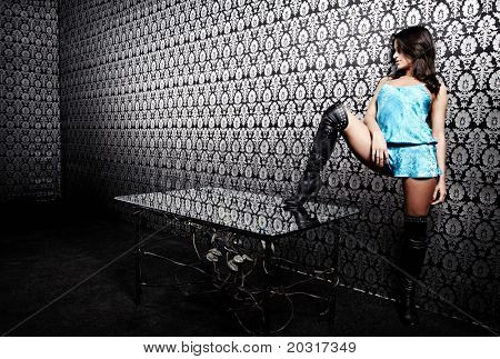 The sexual girl with the put foot on a table at a wall