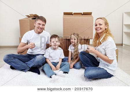 Families with children drinking tea on a background of cardboard boxes