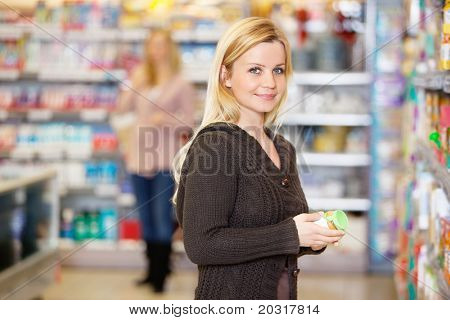 Closeup of a young woman smiling while shopping in the supermarket