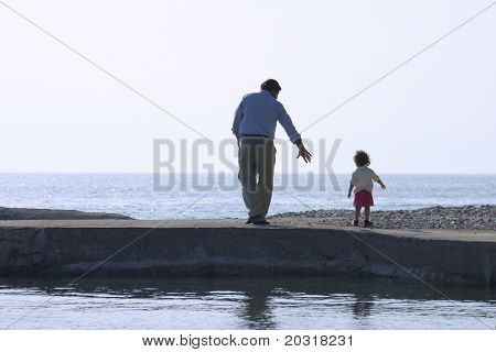 father and son by the sea,reflections in the water
