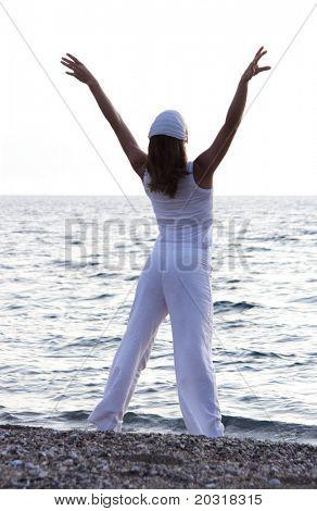 Woman stretching am Strand bei Sonnenaufgang