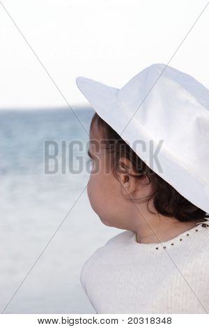 girl wearing hat by the sea