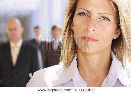 mulher de negócios confiante com a equipe por trás dela