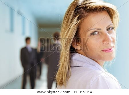 businesswoman looking over her shoulder, blurry businessmen in the background