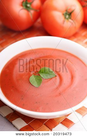 creamy tomato soup with basil leaves as garnish