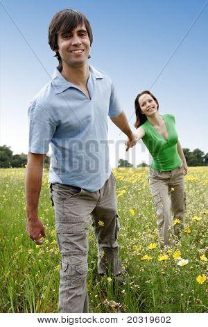 paar Holding hands in einem Blume-Feld