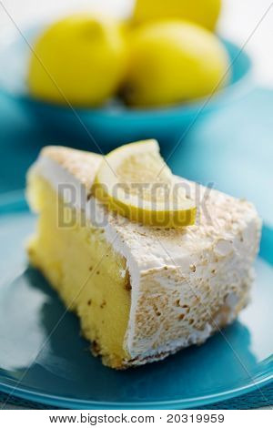 slice of lemon pie with lemons in the background, focus is on the front of the cake