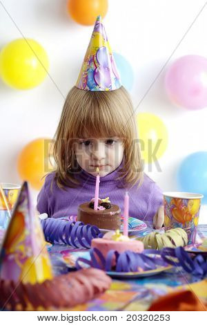 little girl waiting to blow out the candle in her cake